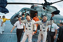 Lovell and Aldrin in space suits without helmets or gloves. They stand on a wooden deck, waving baseball caps. In the background is a Sea King helicopter