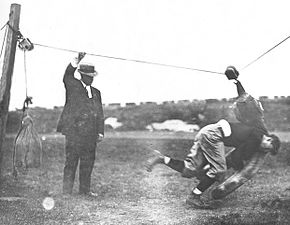 Thorpe tackling a dummy that is made of weights and pulley on wire, with Coach Warner, 1912 Glenn Warner, Jim Thorpe tackling a dummy.jpg