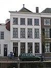 foto van Vier traveeën breed woonhuis met gepleisterde lijstgevel, lijst met klosjes. Vensters met hardstenen onderdorpels. Voordeuromlijsting. Stoeppalen. Dakpiron