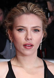 An image of Scarlett Johansson posing for the camera with paparazzi in the background.