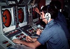 A sailor in a blue shirt sits at a console, it has a large circular screen and switches.