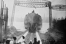 A black and white photograph showing a ship's hull with no superstructure sliding down a slipway into a waterway