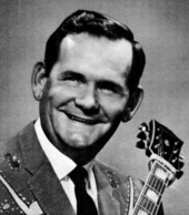 A dark-haired man in a sports jacket and tie holding a guitar.