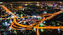 Night photograph looking down at a large elevated road interchange; many billboards along the roads