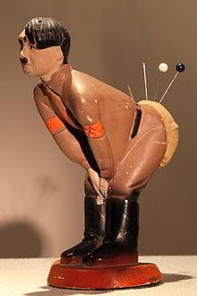 Une photo en couleurs (fond brun clair) d'une statuette en plâtre d'Adolf Hitler, posée sur un support beige. L'homme, de profil, tête nue, porte un uniforme marron clair et des bottes noires. Il est penché vers l'avant (de droite à gauche), les deux mains réunies entre ses genoux. Son derrière est recouvert d'une capote en laine orange dans laquelle sont plantées quatre épingles.