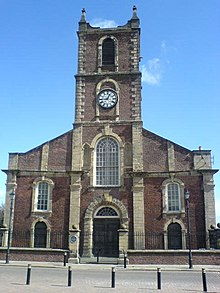 A brick church with stone dressings seen from the south. The west tower has a clock and pinnacles, and along the south face of the body of the church are Georgian-style windows.