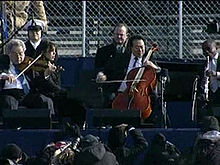 Four male musicians playing a variety of instruments outdoors in front of a chain link fence