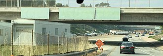 Interstate 710 - Merging onto the northern stub of I-710 in downtown Pasadena. Note dormant construction equipment lining the median, and the road sign structures installed on the overpass without any signs posted