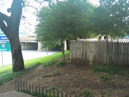 The wooden fence atop the grassy knoll, and the Triple Underpass with the highway sign, which at the time of the assassination read &quotFort Worth Turnpike Keep Right,&quot as seen in the Zapruder film. The knoll is where many conspiracy theorists believe another gunman stood. - Assassination of John F. Kennedy