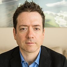 Portrait of author, seasteading evangelist Joe Quirk with short, dark hair wearing a blue shirt and blazer
