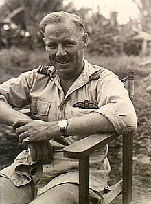 Half-length portrait of seated man in tropical military uniform with pilot's wings on left breast pocket