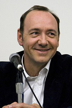 A photograph of Kevin Spacey smiling with a mic