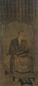 Monk seated on a chair holding a stick-like object in his right hand in three-quarter view. Above the painting there is Chinese text.