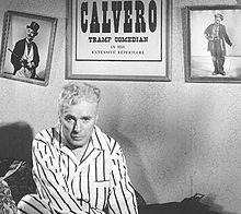 Capture d'écran montrant Chaplin l'air fatigué en pyjama blanc rayé assis dans son lit. Des photographies d'un personnage ressemblant à Charlot sont accrochées sur le mur derrière lui.