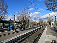 The side and island light rail platforms of Beaverton Transit Center; they are adorned with leafless trees and the left most platform consists of a shelter