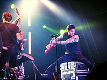 Two guys jumping with instruments in their hands