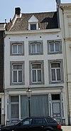 foto van Huis met in de lijstgevel, segmentboogvensters in Naamse steen.
