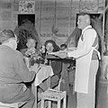 Man in een schort bedient leden van de kibboets bij de viering van sederavond, Bestanddeelnr 255-0664.jpg