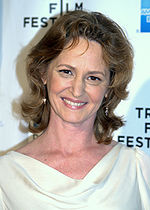 Portrait of a Caucasian woman on her early fifties. She smiles while she looks at the camera. She wears a white blouse and earrings.