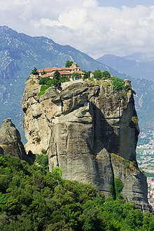 A monastery stands atop a large mountain.