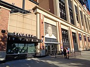 Exterior of a stadium. The admission gate has a large picture of Stengel in a Mets cap over it.
