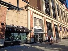 Exteriér stadionu.  Přijímací brána má velký obraz Stengel v čepici Mets nad ním.