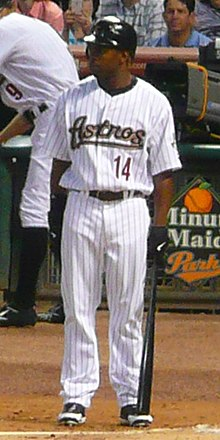 "A dark-skinned man in a white pinstriped baseball uniform stands on the dirt. He holds a black baseball bat in his left hand, and his jersey reads ""Astros"" in script lettering and ""14"" in block print."