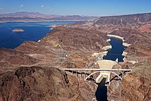 Aerial view of Hoover Dam with Lake Mead behind it and desert landscape