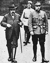 Zwart-witfoto van twee pratende mensen tijdens het lopen: links een man met een zwarte snor met een bril op, gekleed in burgerkleding met een hoed en laarzen;  rechts een man met een witte snor in militair uniform;  achter hen, een derde man, met een zwarte snor, ook gekleed in een militair uniform