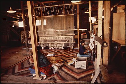 The art of Dine weaving is part of the traditional knowledge of the Navajo people. NAVAJO WOMEN WEAVE A RUG AT THE HUBBEL TRADING POST, FIRST TRADING POST ON THE NAVAJO RESERVATION - NARA - 544416.jpg