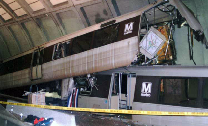 A badly damaged subway car sticks up at an angle where it had partially ridden over another car in an underground station.