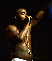 A barebodied Nas singing onstage.
