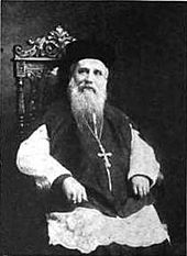 An elderly man with a long beard, a hat, and a crucifix hanging from his neck is sitting on an ornate chair.