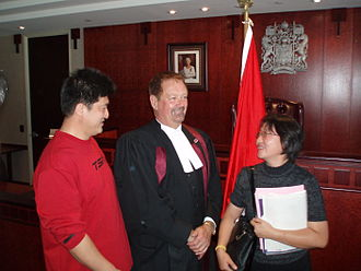 Oath of Citizenship (Canada) - Recent recipients of their Canadian citizenship at the end of a citizenship ceremony, with the citizenship judge, a Canadian flag, and, in the background, a portrait of Queen Elizabeth II and a bas-relief of the Royal Coat of Arms of Canada