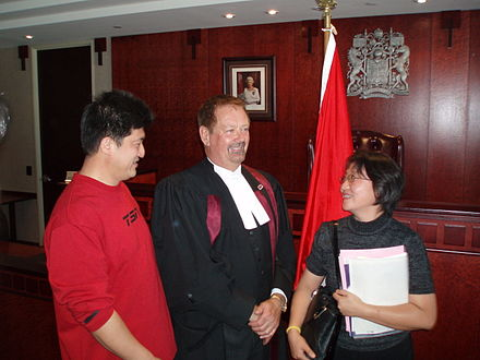 A Canadian courtroom with the arms of Canada, and a photo of the Canadian monarch OathofCitizenship.jpg