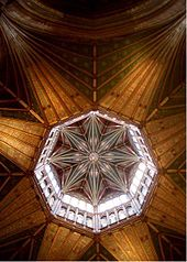 The interior view from beneath an octagonal wooden tower with star shaped vaulting and big windows.