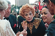 An aged Ball standing in a crowd of celebrities, wearing a black and gold sequinned dress with her characteristic red hair, looking fragile.