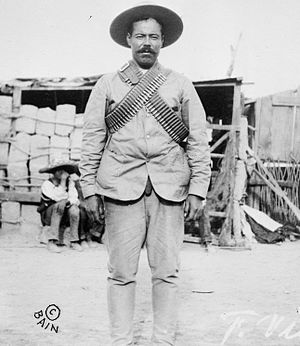 Pancho Villa Expedition - Pancho Villa wearing bandoliers in front of an insurgent camp