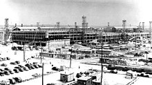 Vista expansiva de un sitio de construcción con muchos autos estacionados, andamios y grúas.  Hay una serie de desmontables en primer plano.