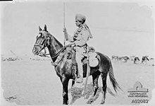 In a black and white photograph, a man wearing a turban and light-coloured tunic sits astride a dark-coloured horse facing left and holds a bayonet in his right hand. He is depicted against a desert landscape.