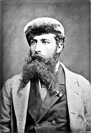 Black and white photograph of a man with a dark, forked beard, wearing a suit, coat and cloth hat.