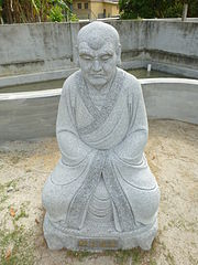 Image of older monk with large eyebrows, sitting, with his hands hidden in his sleeves