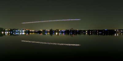 nightshot of a plane over a pond. You can see the landing and position lights as stripes.