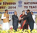 Pranab Mukherjee presenting the National Award for Teachers-2014 to Shri B Ganeshappa, Karnataka, on the occasion of the 'Teachers Day', in New Delhi. The Union Minister for Human Resource Development, Smt. Smriti Irani.jpg