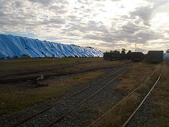 Bagasse - Bagasse, covered with blue plastic, outside a sugar mill in Proserpine, Queensland