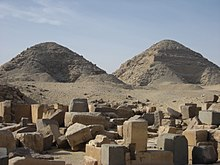 Photograph of two pyramids at Abusir. On the left, the shorter ruined Pyramid of Nyuserre. On the right, the taller pyramid of Neferirkare.