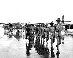 Uniformed personnel marching on airfield with two twin-engined transport aircraft in background