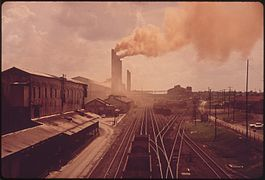 RED-ORANGE SMOKE POURS FROM STEEL PLANT CHIMNEYS ON EDGE OF RAILROAD - NARA - 545507.jpg