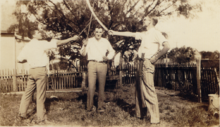 Sepia toned photograph of three teenagers posing with swords.