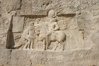 Philip the Arab -  Rock-face relief at Naqsh-e Rustam of Shapur I (on horseback) with Philip the Arab and Emperor Valerian kneeling in surrender to the Persian king.